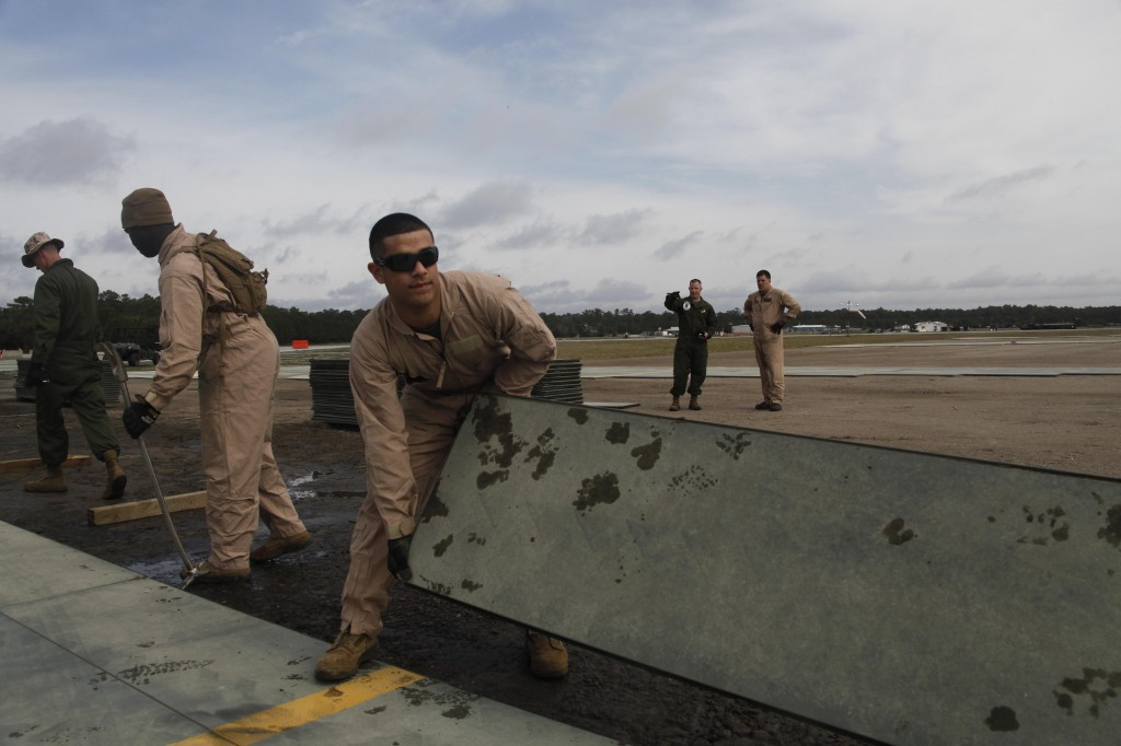 Marine Wing Support Squadron 271 engineers lift a 155-pound piece of aluminum matting on the flight line at Marine Corps Auxiliary Landing Field Bogue March 18. The Marines will replace approximately 200,000 square feet of matting during the upgrade. (Photo by Lance Cpl. Glen E. Santy)