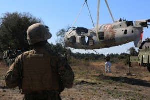 Staff Sgt. William Ford supervises an aircraft suspension during an aircraft recovery training exercise at Marine Corps Auxiliary Landing Field Bogue, N.C., Feb. 2, 2016. Aircraft rescue and firefighting Marines, heavy equipment operators, bulk fuels specialists, motor transportation Marines and combat engineers with Marine Wing Support Squadron 274 worked hand-in-hand to retrieve a simulated downed aircraft. They were given a scenario and were tasked to provide a security perimeter around the aircraft while securing and transporting the aircraft in a safe and effective manner. The ability to retrieve aircraft without the aid of outside resources increases the unit's effectiveness and their expeditionary capabilities. Ford is the motor transportation operations chieff with MWSS-274. (U.S. Marine Corps photo by Cpl. N.W. Huertas/ Released)